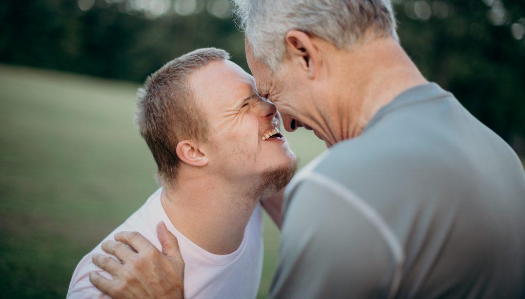 Junge mit Behinderung und älterer Mann in Umarmung