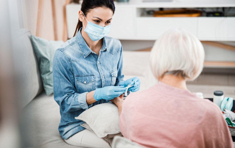 Frau mit Maske im Pflegeheim bei der Arbeit