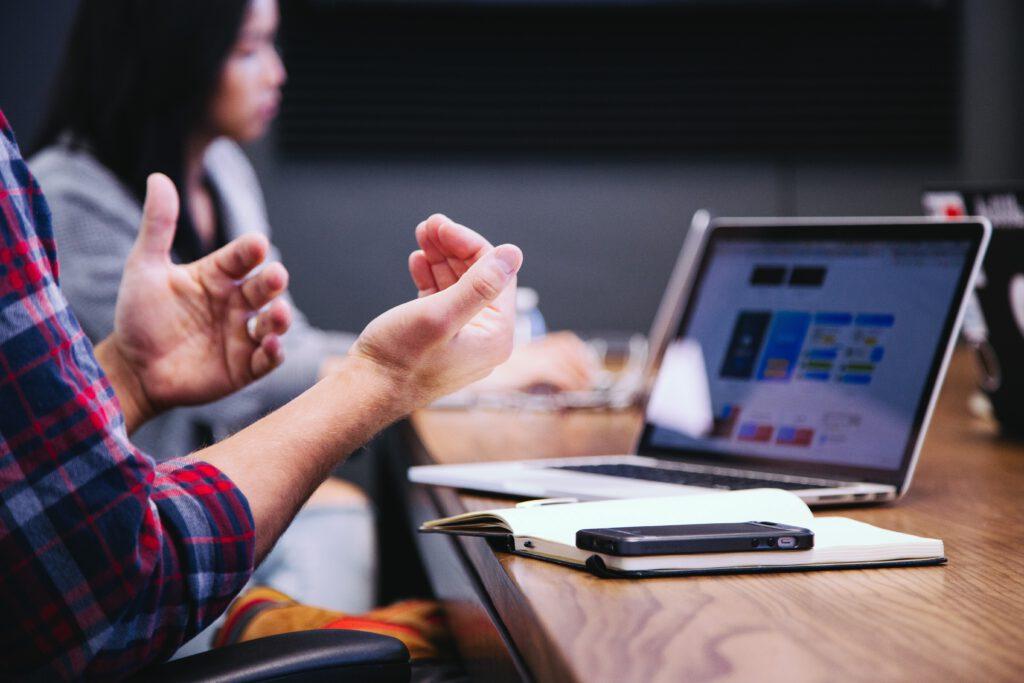 Gestikulierende Hände vor Laptop